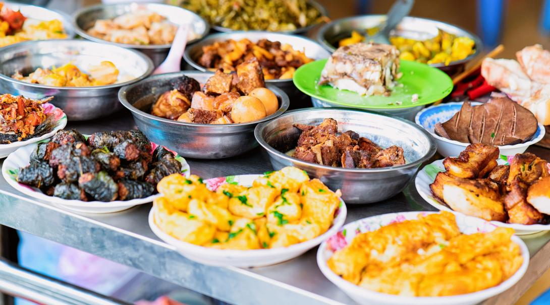 Street food laid out on tables at the local market in Vietnam.